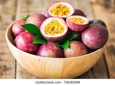 Fresh ripe passion fruit on wood bowl put on wood table in vintage tone style for background or wallpaper so sweet and sour. Passion fruit is tropical fruit.