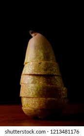 Fresh ripe pear with soft skin cut into slices on a wooden board with a black background in soft side lighting