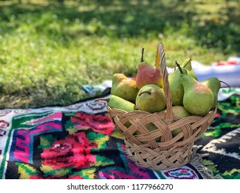 fresh ripe pears in a basket for picnic at a  park