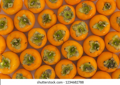 Fresh ripe persimmons placed on table in market. Organic persimmon fruit in pile at local farmers market. Persimmons background.