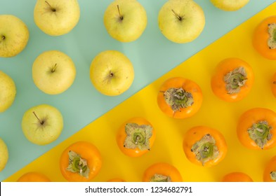 Fresh ripe persimmons and yellow apples bright split color background. Organic persimmon fruit and apple flat lay vibrant duotone background.