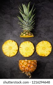 Fresh ripe pineapple cross sections on dark background, vertical composition, tp view