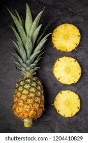 Fresh ripe pineapple and cut cross sections on dark background, vertical composition, top view