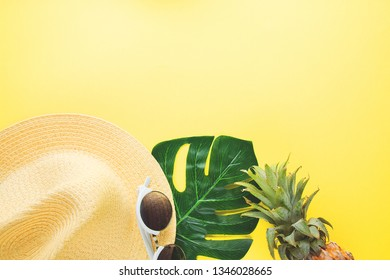 Fresh ripe pineapple glasses hat and leaf of monstera tree on color background, top view.