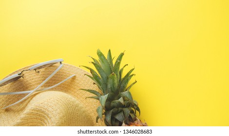 Fresh ripe pineapple glasses hat on color background, top view.