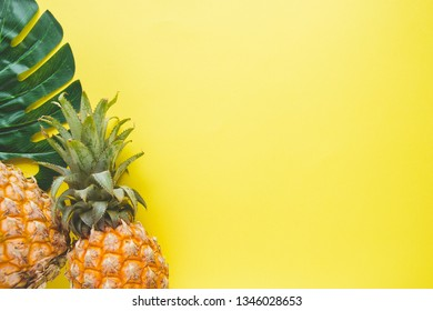 Fresh ripe pineapple and leaf of monstera tree on color background, top view.