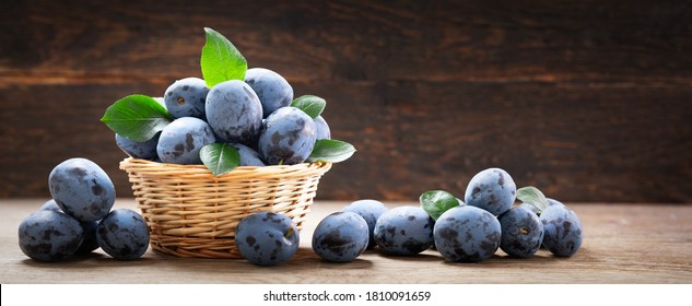 fresh ripe plums with leaves in a basket on a wooden table