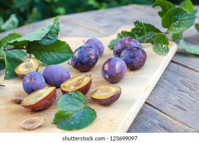 Fresh ripe plums on wooden cutting board and table in summer