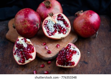 fresh ripe pomegranate on a dark wooden background garnet in the section. pomegranate