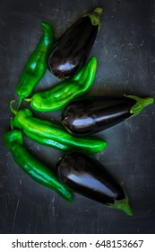Fresh ripe purple eggplants green italian peppers composition on dark background, healthy eating concept, food ingredients, vegetarian, vegan, minimalistic clean modern style, close up