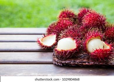Fresh ripe rambutans on wooden background. Delicious rambutan sweet fruit.