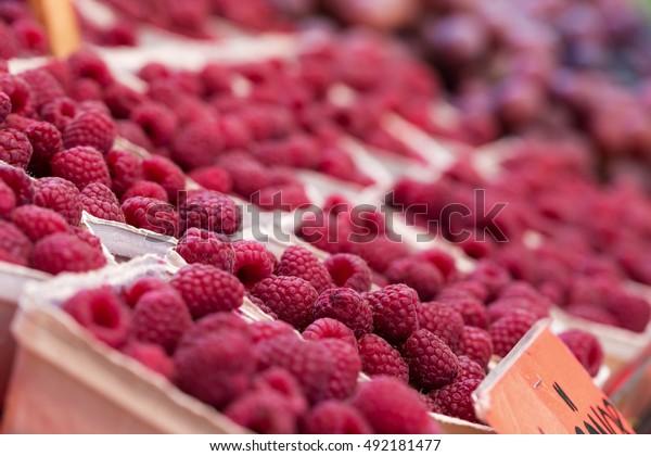 Fresh ripe raspberries in carton boxes on sale at farms market, shallow depth