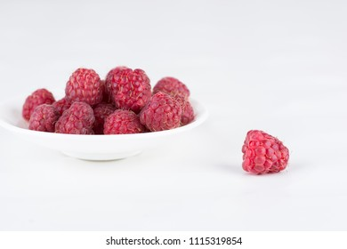 Fresh ripe raspberries on a plate on a white background. Close-up, minimal concept of fashion food