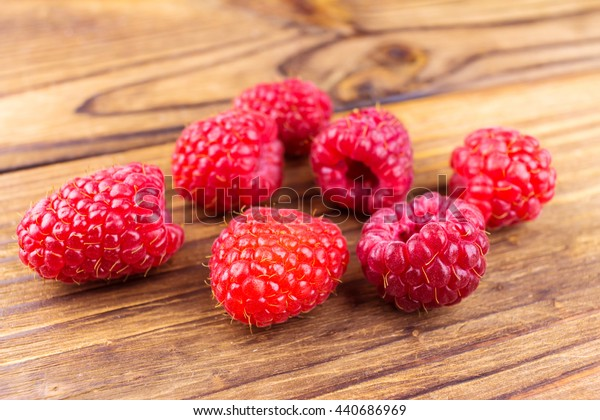 Fresh ripe raspberries on rustic wooden background