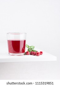 Fresh ripe raspberries and raspberry juice in a glass cup on a white background. Close-up, minimal concept of fashion food