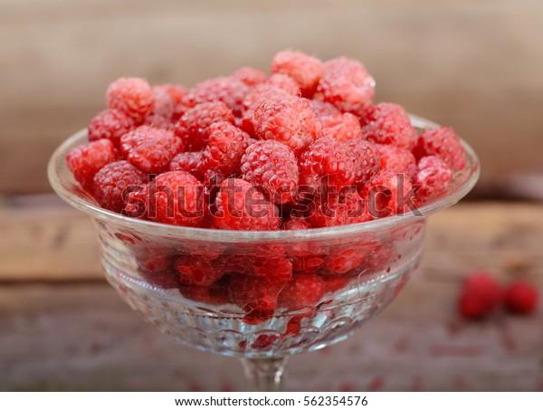 Fresh ripe raspberries in vintage crystal vase on old rustic wooden table
