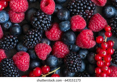 Fresh ripe raspberry red currant and blueberry berries on black slate board. Gray stone background.  Top view.