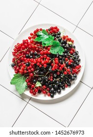Fresh ripe red and black currant on light background, top view