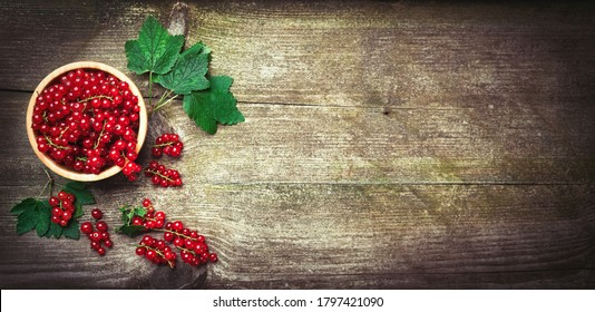 Fresh ripe red currant berries with leaves in a bowl on rustic old wooden table. Healthy organic food, summer vitamins, BIO viands, natural background. Copy space for your advertising text message.