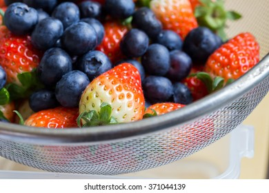 Fresh ripe red strawberries and blueberries in sieve