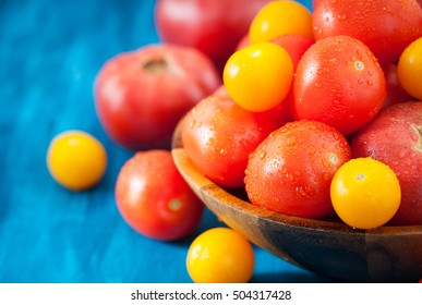 Fresh ripe red and yellow tomatoes in wooden bowl