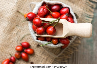 Fresh ripe rose hips in burlap bag on the rustic background