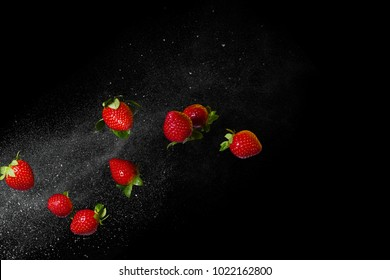 Fresh ripe strawberries flying on a black background. Stop the moment. Free space