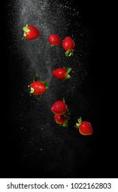 Fresh ripe strawberries flying on a black background. Stop the moment