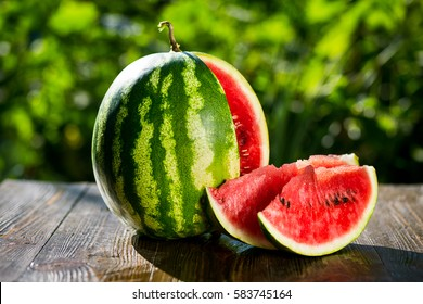 Fresh ripe striped sliced watermelon on wooden background