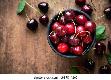 Fresh ripe sweet cherries in a bowl with droplets of water. Overhead view on dark rustic wooden background, closeup