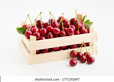 Fresh, ripe sweet cherries in small wooden crate on white background.