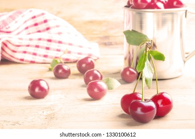 Fresh ripe sweet cherry in the steel mug on the wooden table. Rustic style foto