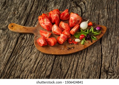 Fresh ripe tomatoes on a cutting board with basil, salt and pepper. Healthy, diet or vegetarian food concept. Rustic background with space for text.