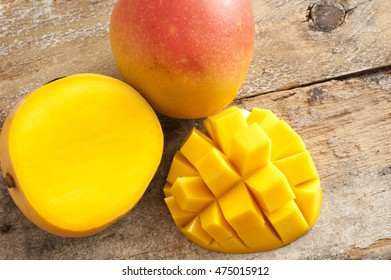 Fresh ripe tropical mango whole and sliced through to show the juicy flesh with a one section cut into a decorative hedgehog pattern , overhead on rustic wood