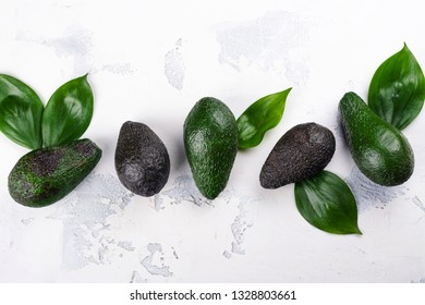 Fresh ripe whole and cut avocado on white background. Copy space