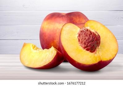 Fresh ripe whole and cut tasty peach fruit on the desk