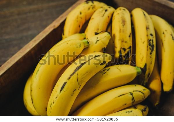 Fresh ripe yellow bananas in wicker basket on wooden background