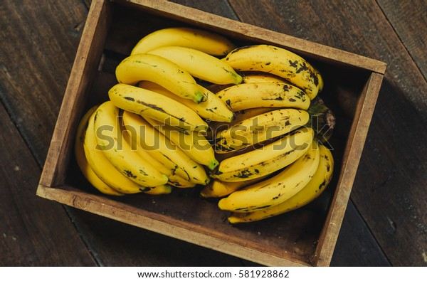 Fresh ripe yellow bananas in wicker basket on wooden background