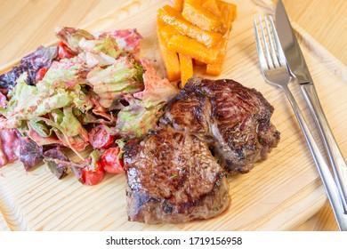 Fresh roasted bone-in ribeye steak with sweet potatoea and mix salad