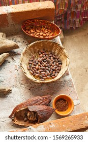 Fresh and roasted cocoa beans in the basket and cocoa power in a salad bowl lying on a brick table. Top view.