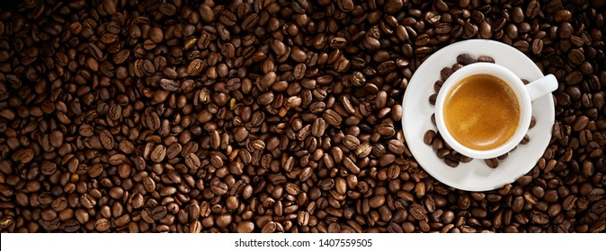 Fresh roasted coffee bean background with a cup of hot frothy espresso placed to the right side in a wide panorama banner with copy space