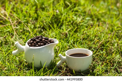Fresh roasted coffee beans and fresh coffee in ceramic set on the lawn.