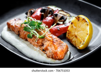 Fresh roasted grilled salmon fillet on a sour cream sauce on a black frying pan served with grilled zucchini, aubergine and champignon mushrooms with baked lemon and covered with green cereal sprouts