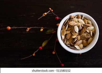 fresh roasted pumpkin seeds in bowl on wood table