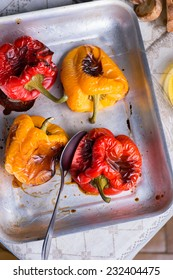 Fresh roasted red and yellow peppers on metal tray, selective focus, top view