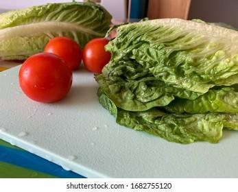 Frischer romagnolischer Salat und reife Kirschtomaten, die frisch auf dem Schneidebrett gespült werden, Kochen von frischem Gemüsesalat