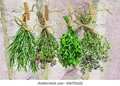 fresh rosemary, thyme and parsley hanging on a string, in front of a wall made of sandstone