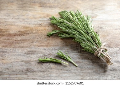 Fresh rosemary twigs tied with twine on wooden table