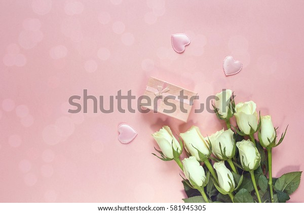 Fresh roses flowers with gift box and hearts on a pink background. Place for text. Post card, greeting card mock up.