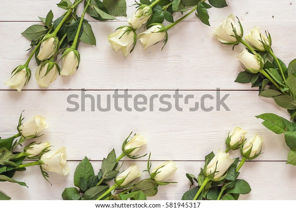 Fresh roses flowers on white painted wooden background. Place for text. Post card, greeting card mock up.